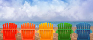 vacation-beach-chairs-sand-rainbow-colors-wooden-lined-up-along-water-shore-there-copyspace-clouds-42681503